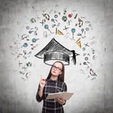 Serious girl and education icons on concrete Stock Image