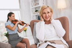 Serious girl enjoying her melody. Bad play. Negative delighted women wrinkling forehead while covering her ears royalty free stock photo