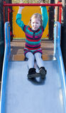 Serious girl girl on children chute ready to slide in springtime Royalty Free Stock Photography