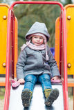 Serious girl on children chute ready to slide Royalty Free Stock Photo