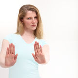 Serious girl holding out her hand signaling stop. Pretty girl with a serious look holding out her hand signaling stop Stock Photo