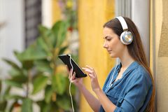 Serious girl listening and watching tablet content stock image