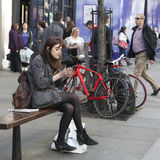 Serious girl with long hair sitting on a bench near Covent Garden Royalty Free Stock Photo