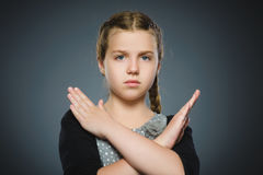 Serious girl making X sign with her arms to stop doing something.  Royalty Free Stock Photos