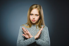 Serious girl making X sign with her arms to stop doing something.  Royalty Free Stock Images