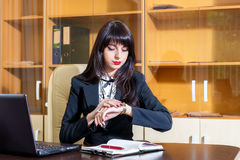 Serious girl in office looking at her watch Royalty Free Stock Photography