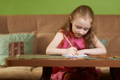 Serious girl painting  on paper Stock Photo