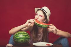 Serious girl with pink make up, wearing jeans, hat and top, posing at red studio background near wooden box, holding slice. Watermelon and eat it, smile royalty free stock image