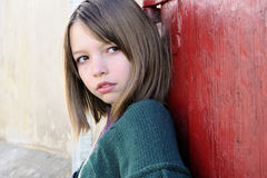 Serious girl posing with red door in background Royalty Free Stock Photos