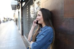Serious girl profile talking on phone in the street stock image