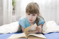 Serious girl reading a book lying in bed Royalty Free Stock Photos