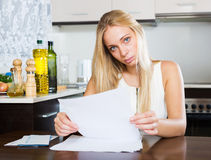 Serious  girl reading document at home Royalty Free Stock Photography
