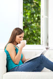 Serious girl reading magazine on sofa. Stock Images