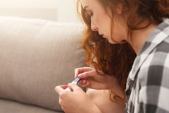 Serious girl reading the results of her pregnancy test. Serious redhead girl checking her recent pregnancy test, sitting on beige couch at home, copy space, side stock image