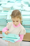 Serious girl recounts school notebook in store Stock Image