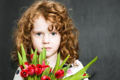Serious girl with red tulips Stock Image