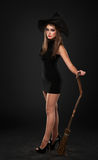 The serious girl is standing with the broom. In the studio Stock Image