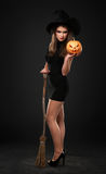 The serious girl is standing with the pumpkin Royalty Free Stock Photo