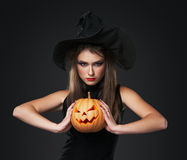The serious girl is standing with the pumpkin Royalty Free Stock Photography