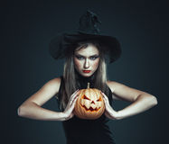 The serious girl is standing with pumpkin Royalty Free Stock Photos