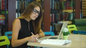 Serious girl student working at laptop with book in the city library stock footage