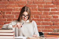 Serious girl studying at desk with book free space. Serious girl studying at desk with books free space. Student girl sitting at table with textbooks in library Stock Photos