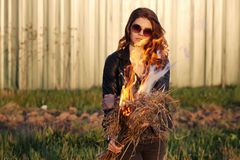 Serious girl in sunglasses standing in a black jacket with a fire in his hands Outdoors Royalty Free Stock Image