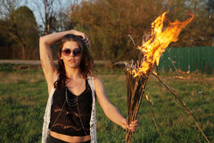 Serious girl in sunglasses standing in a black jacket with a fire in his hands Outdoors Stock Photography