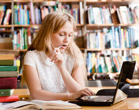 Serious girl typing on notebook in library Stock Photos
