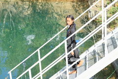 Serious girl in wetsuit. Serious tropical girl - young indonesian woman dressed up into wetsuit and ready for scuba  diving descending on iron stairs into water Stock Photography