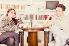 Serious glamor couple sitting on armchairs in the library Stock Images
