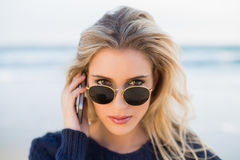 Serious gorgeous blonde on the phone looking over her sunglasses Royalty Free Stock Images
