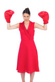 Serious gorgeous brunette in red dress wearing boxing gloves Stock Photo