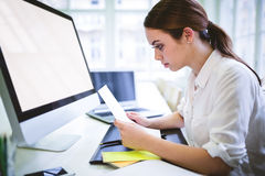 Serious graphic designer looking at document. At desk in creative office Stock Photos