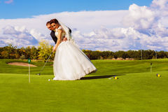 Serious groom and bride playing golf Royalty Free Stock Image