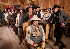 Serious Group of People in Old West Tavern Stock Image