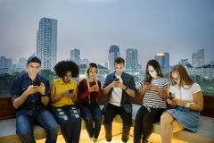 Serious group of young adults using smartphones in the cityscape stock photography