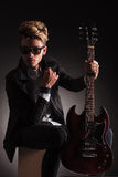 Serious guitarist wearing sunglasses is sitting Royalty Free Stock Photography