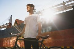Serious boy with brown hair standing with bicycle and thoughtfully looking aside. Young man in white t-shirt standing. Serious guy with brown hair standing with Royalty Free Stock Photo