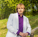 Serious guy in the park a white suit and purple Stock Photo
