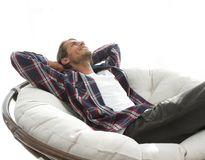 Serious guy rests sitting and dreaming in a large comfortable chair. Photo has a blank space for text Stock Image