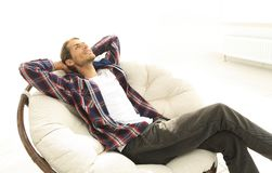 Serious guy rests sitting and dreaming in a large comfortable chair. Photo has a blank space for text Stock Photography