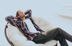 Serious guy rests sitting and dreaming in a large comfortable chair. Photo has a blank space for text Royalty Free Stock Photo