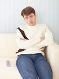 Serious guy sits on sofa with remote control Stock Photo