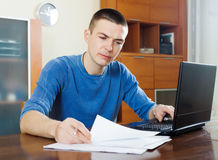 Serious guy staring financial documents Stock Images