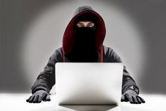 Serious hacker stealing information from laptop stock images