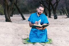 Serious handsome bearded man in blue kimono sitting, leafing through large book stock photography