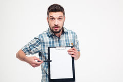 Serious handsome bearded man pointing on blank clipboard Stock Image