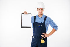 Serious handsome builder showing blank piece of paper on clipboard Royalty Free Stock Images