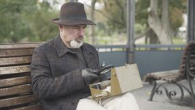 Serious handsome Caucasian spy or intelligencer examining box with novichok using magnifying glass. Portrait of